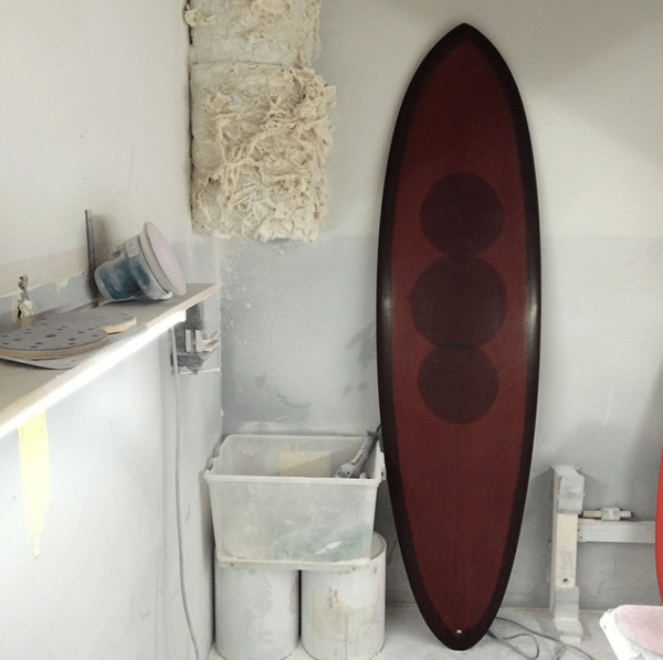 Brown polished surfboard inside the sanding bay