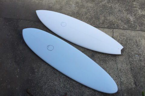 Two blue PCC etched surfboards on the ground